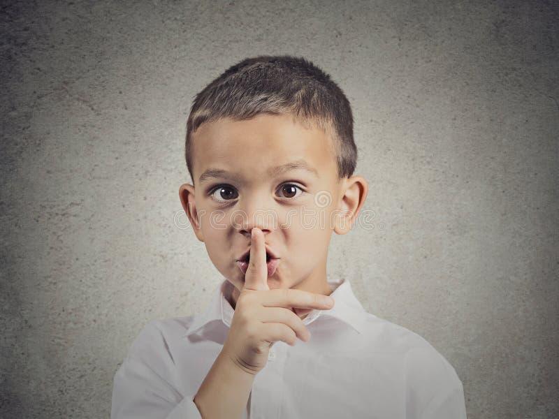 Muchacho que coloca el finger en los labios, gesto reservado imagenes de archivo