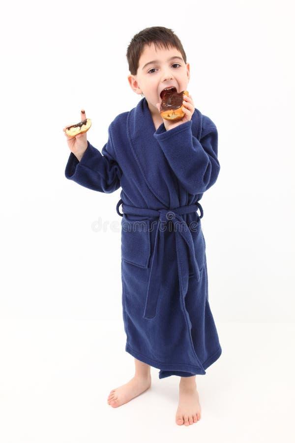 Muchacho que come el buñuelo foto de archivo libre de regalías