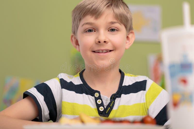 Muchacho que come el desayuno en sala de clase fotografía de archivo libre de regalías