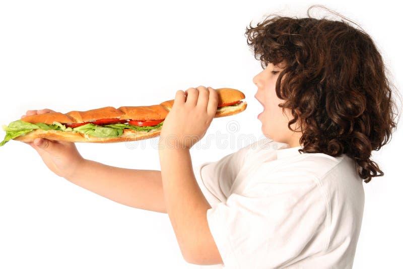 Muchacho que come el emparedado grande fotografía de archivo