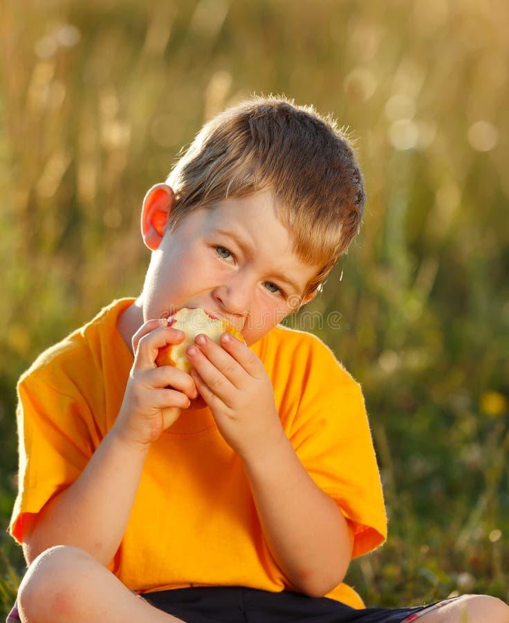 Muchacho que come la manzana foto de archivo