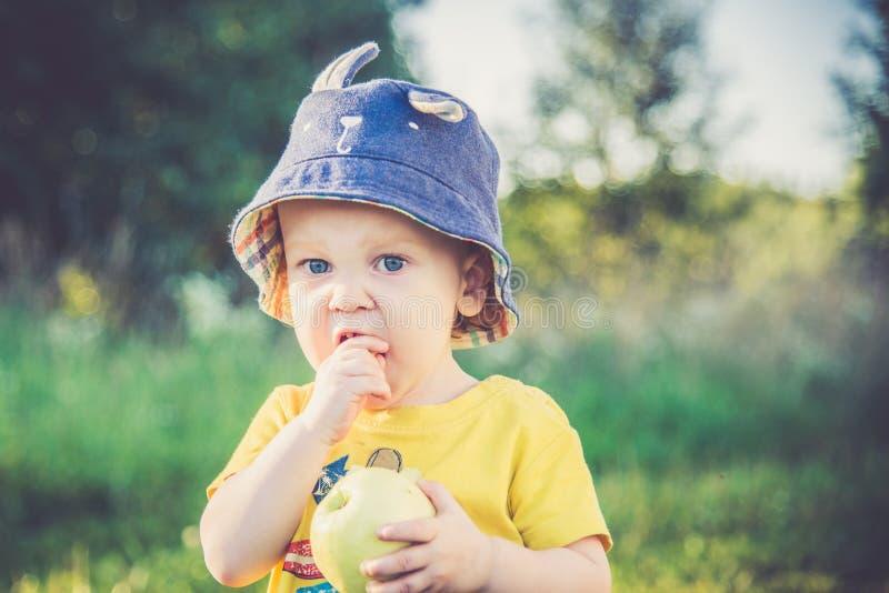 Muchacho que come la manzana sabrosa imagen de archivo libre de regalías