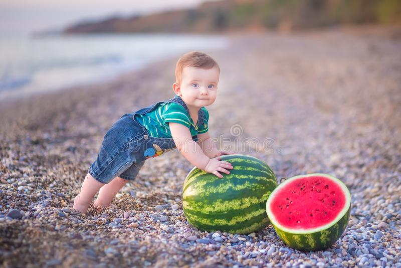 Muchacho que come la sandía en la playa, verano que disfruta de día hermoso cerca del océano foto de archivo libre de regalías