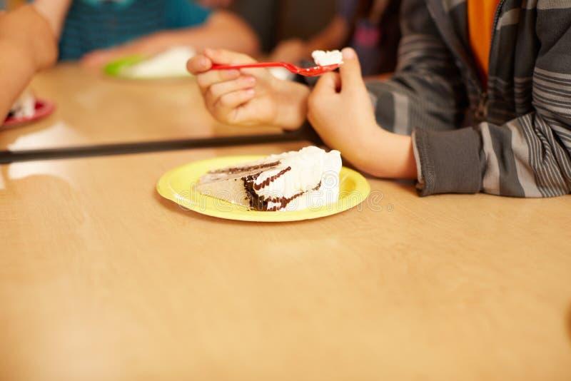 Muchacho que come la torta con helado en el aniversario fotos de archivo libres de regalías