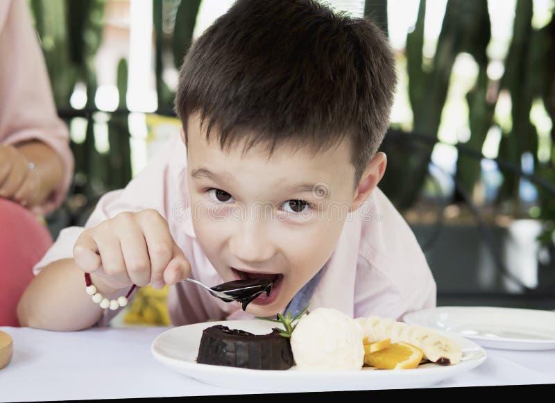 Muchacho que come la torta de la lava del chocolate feliz imagen de archivo libre de regalías