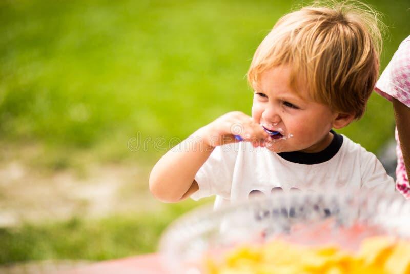 Muchacho que come la torta en una fiesta de cumpleaños exterior imagen de archivo
