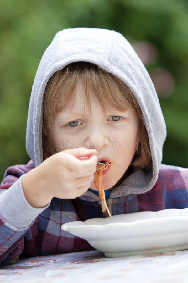 Muchacho que come las pastas imagen de archivo