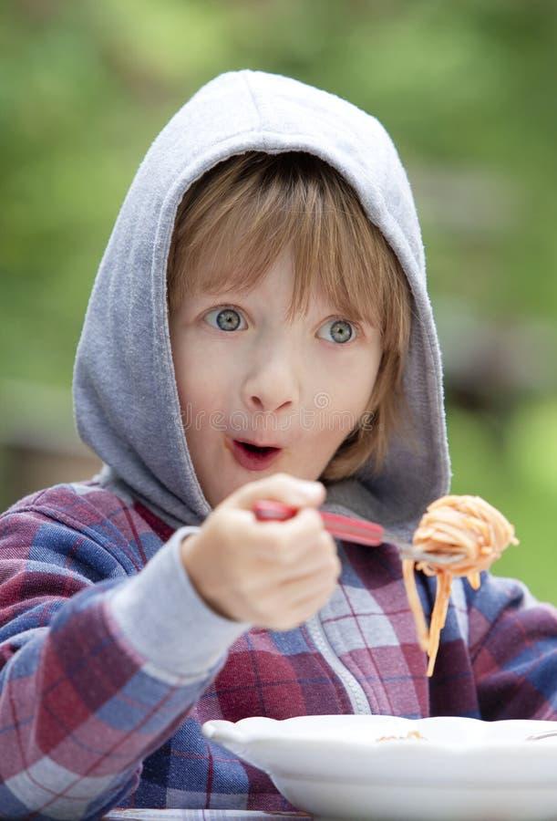 Muchacho que come las pastas fotografía de archivo libre de regalías