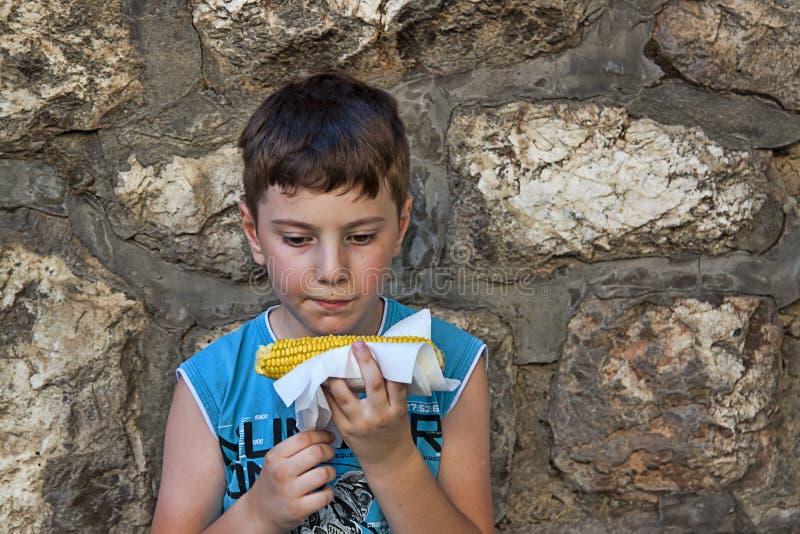 Muchacho que come maíz imagenes de archivo