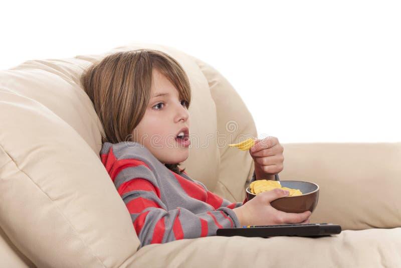 muchacho que come microprocesadores y que mira la televisión foto de archivo libre de regalías