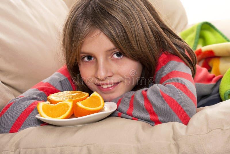 Muchacho que come naranjas frescas fotos de archivo