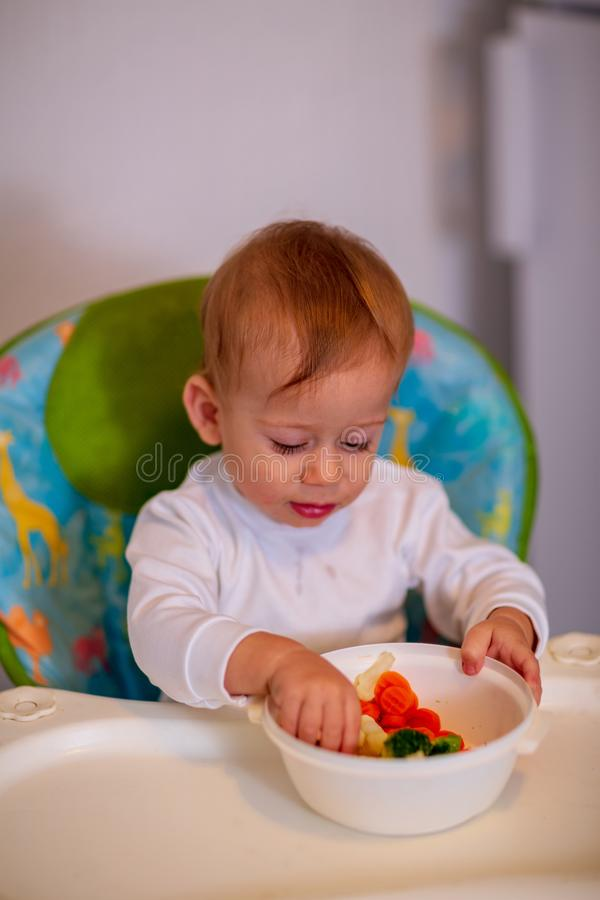 Muchacho que come verduras sanas en la cocina fotos de archivo