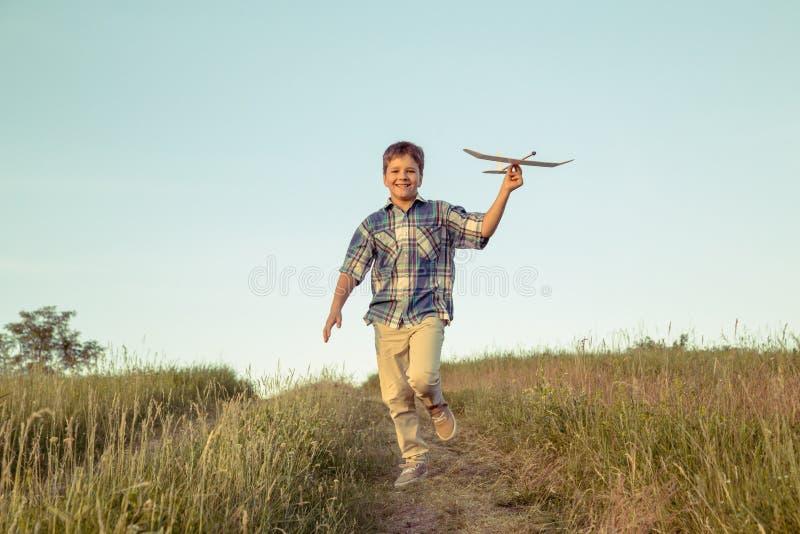 Muchacho que corre con su aeroplano en el campo verde foto de archivo