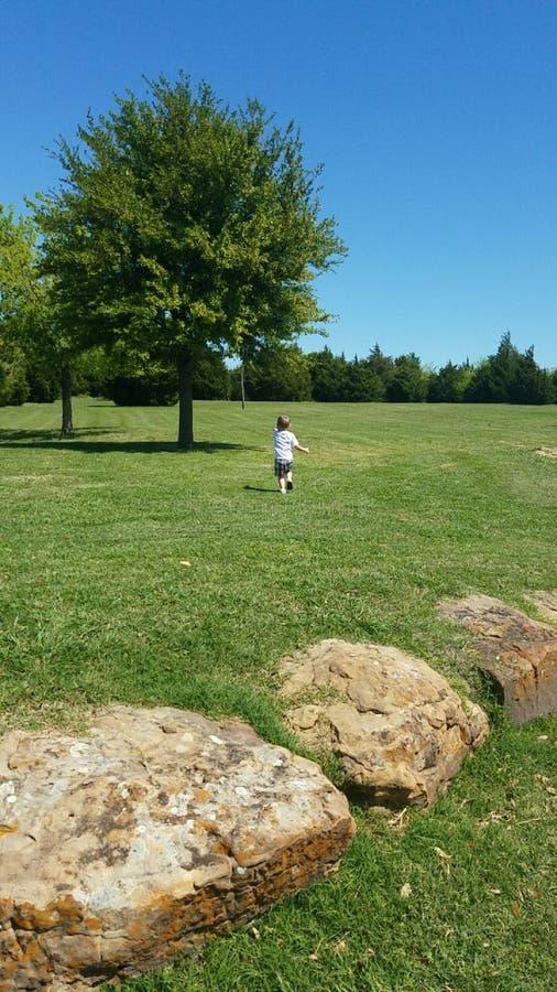 Muchacho que corre en parque imagenes de archivo
