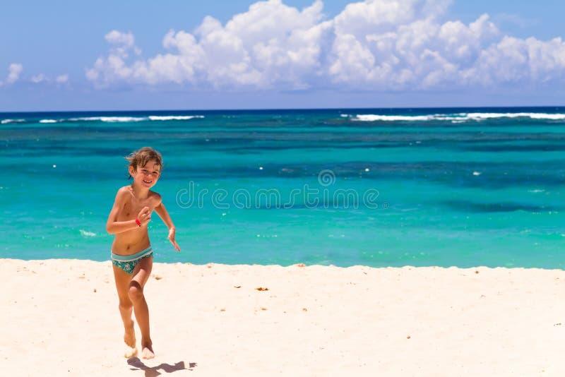 Muchacho que corre en una playa tropical foto de archivo libre de regalías