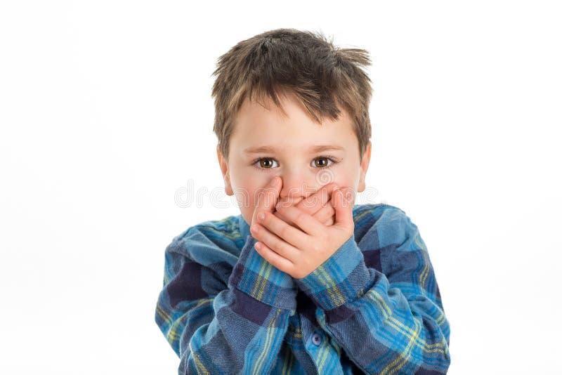 Muchacho que cubre su boca foto de archivo libre de regalías
