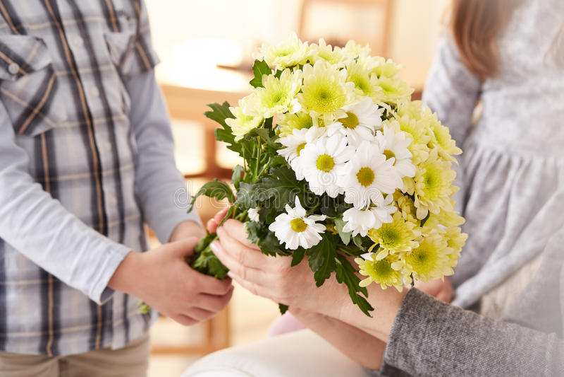 Muchacho que da un manojo de flores fotos de archivo libres de regalías
