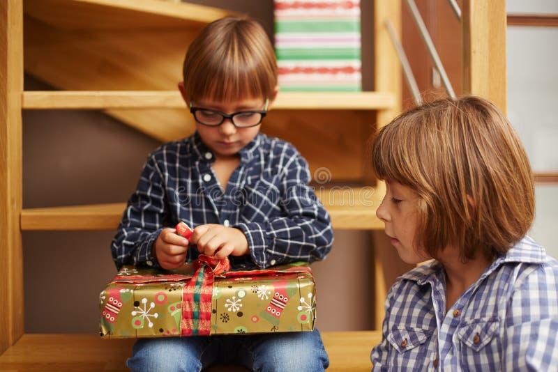 Muchacho que desempaqueta un regalo de Navidad foto de archivo
