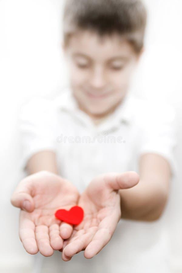 Muchacho que detiene a la tarjeta del día de San Valentín roja del amor del corazón foto de archivo