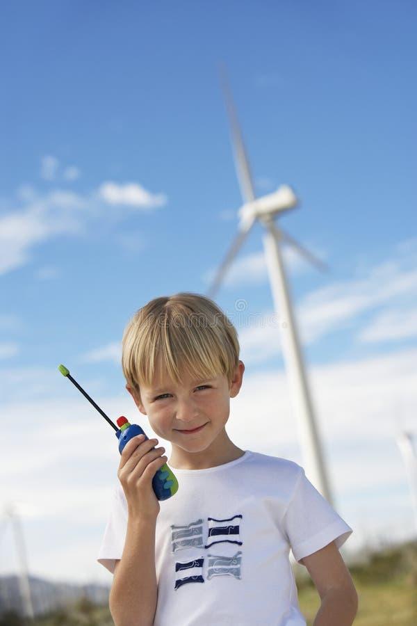 Muchacho que detiene a Toy Walkie-Talkie At Wind Farm imagen de archivo libre de regalías
