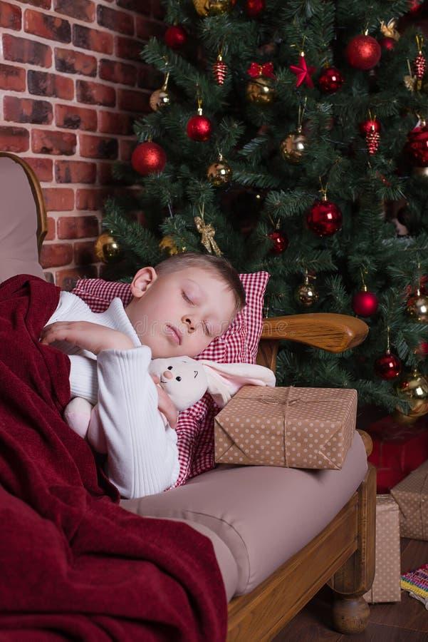 Muchacho que duerme en el sofá cerca del árbol de navidad con los regalos imagenes de archivo
