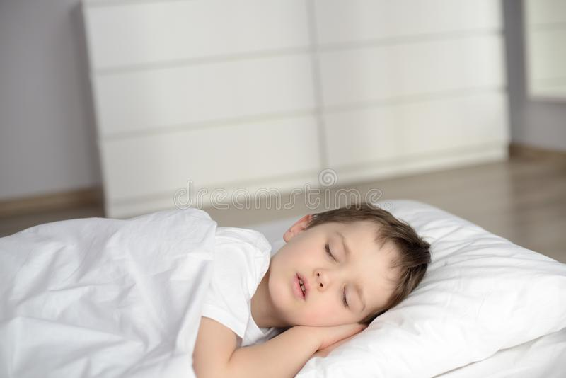 Muchacho que duerme en la cama, hora de acostarse feliz en el dormitorio blanco foto de archivo