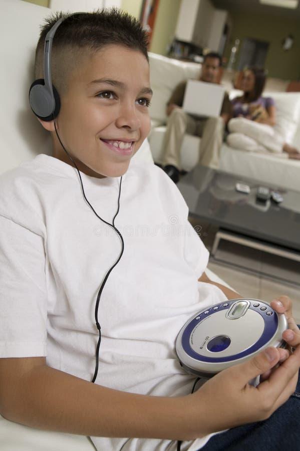 Muchacho que escucha la música en el reproductor de CD portátil en sala de estar fotos de archivo
