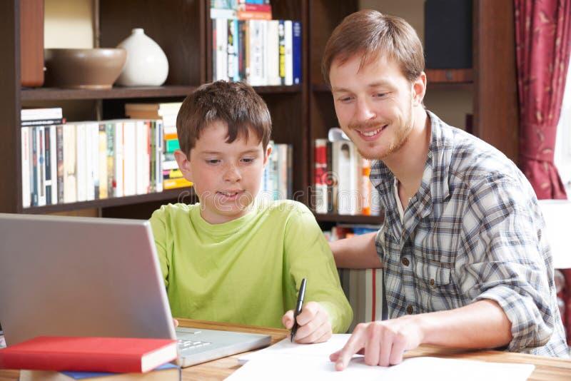 Muchacho que estudia con el profesor particular casero imagen de archivo