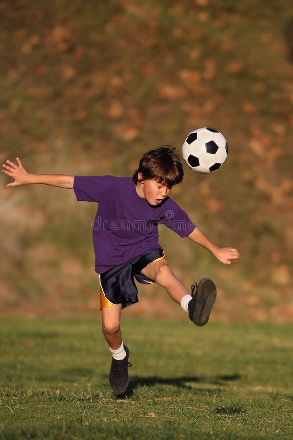 Muchacho que golpea el balón de fútbol con el pie fotografía de archivo