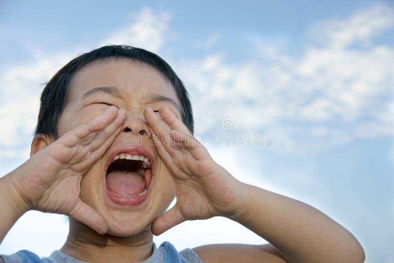 Muchacho que grita con las manos como trompeta fotografía de archivo