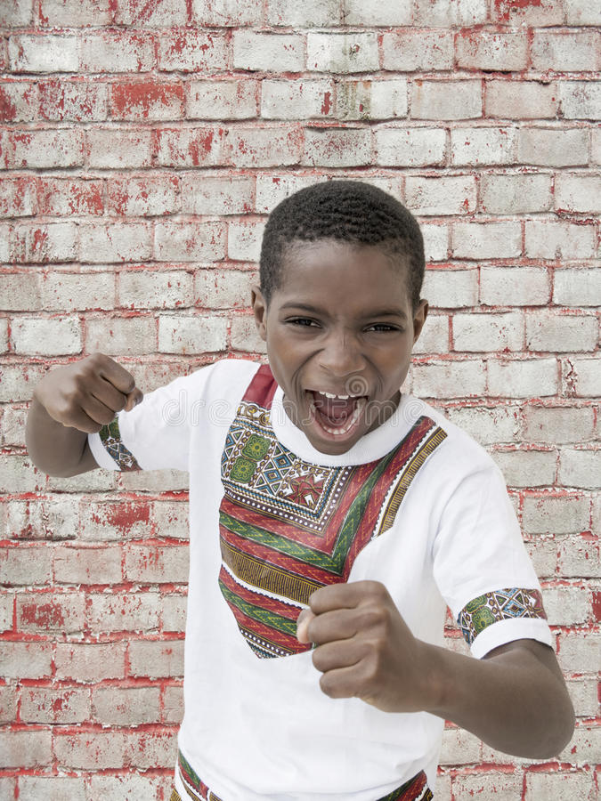 Muchacho que grita, puños apretados, diez años del Afro imágenes de archivo libres de regalías
