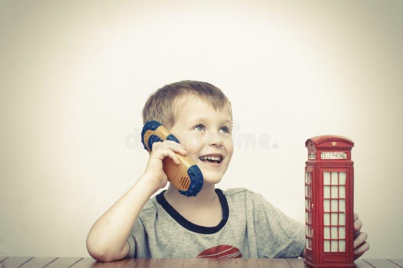 Muchacho que habla en el teléfono y la cabina de teléfono roja fotos de archivo