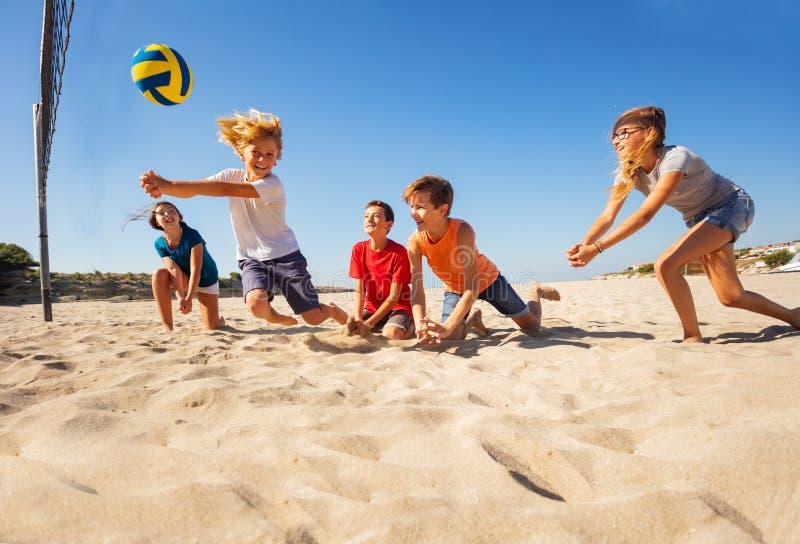 Muchacho que hace el paso del topetón durante partido de balonvolea de playa imágenes de archivo libres de regalías