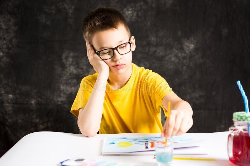 Muchacho que hace un dibujo colorido en casa imagen de archivo libre de regalías