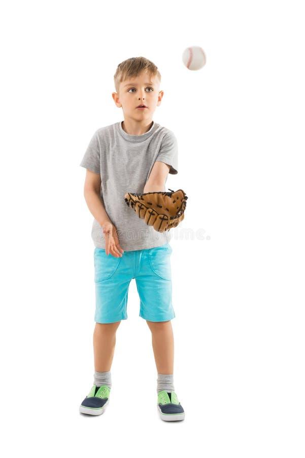 Muchacho que intenta coger béisbol en su guante foto de archivo