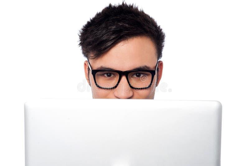 Muchacho que intenta ocultar su cara detrás del ordenador portátil fotografía de archivo libre de regalías