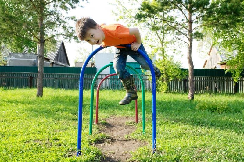 Muchacho que juega al aire libre Niño en el patio, actividad de los niños Niño que se divierte Niñez sana activa fotografía de archivo libre de regalías
