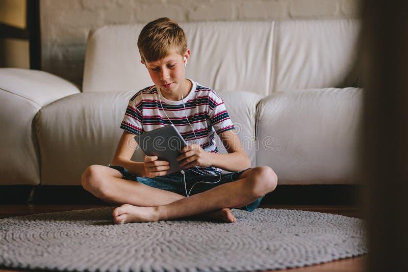 Muchacho que juega al juego online en la tableta en casa fotografía de archivo