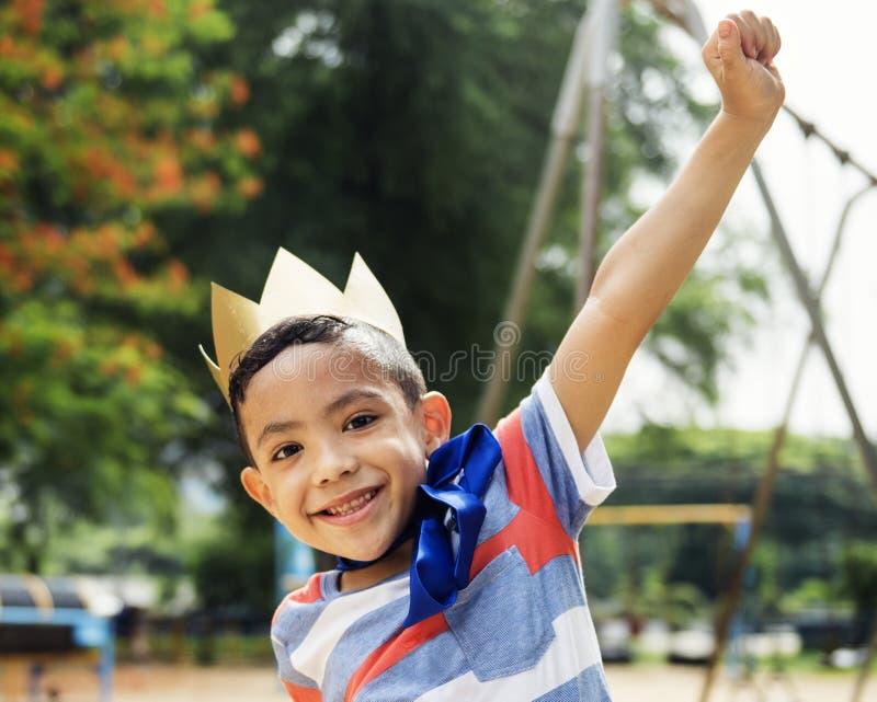 Muchacho que juega al rey en un patio foto de archivo