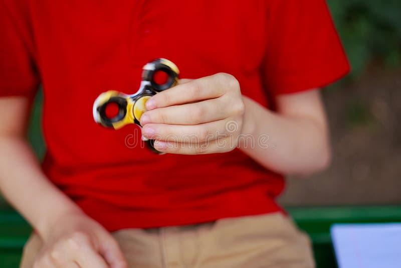 Muchacho que juega con el hilandero de la persona agitada, cierre para arriba Niñez, artilugios, e fotos de archivo libres de regalías