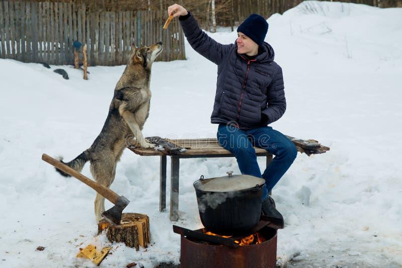 Muchacho que juega con el perro en el pueblo en invierno foto de archivo