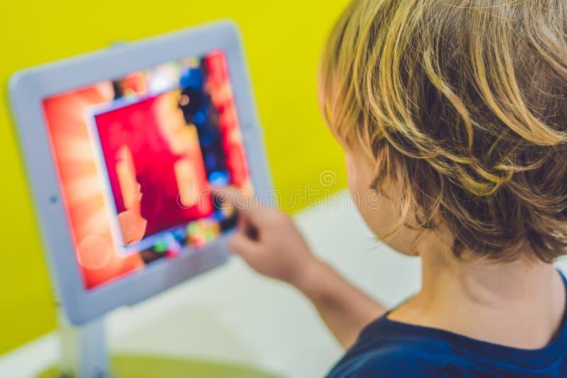 Muchacho que juega con la tableta digital Niños y concepto de la tecnología imagen de archivo