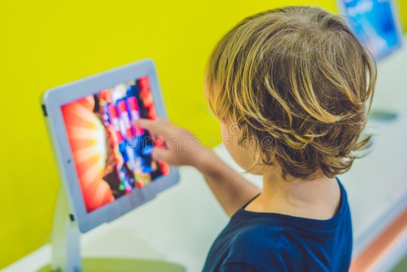 Muchacho que juega con la tableta digital Niños y concepto de la tecnología fotos de archivo libres de regalías