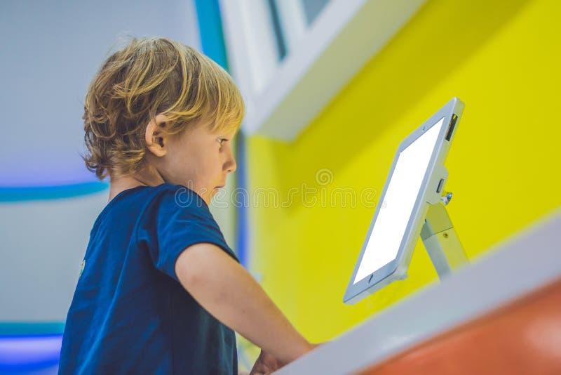 Muchacho que juega con la tableta digital Niños y concepto de la tecnología foto de archivo