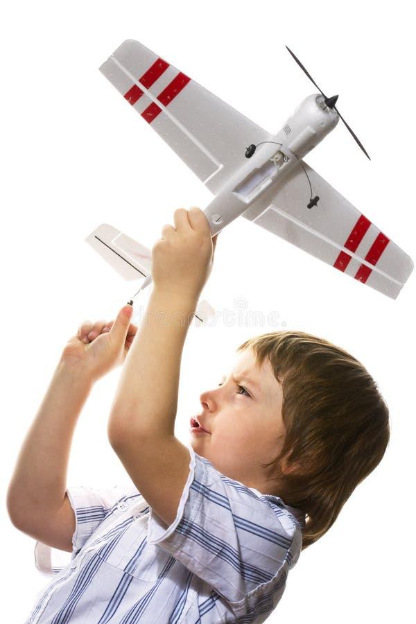 Muchacho que juega con un aeroplano del juguete fotos de archivo