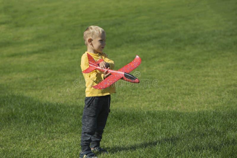 Muchacho que juega con un aeroplano rojo imagen de archivo libre de regalías
