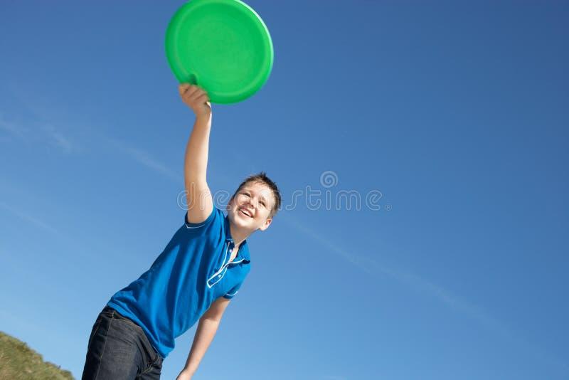Muchacho que juega el disco volador en la playa fotos de archivo libres de regalías