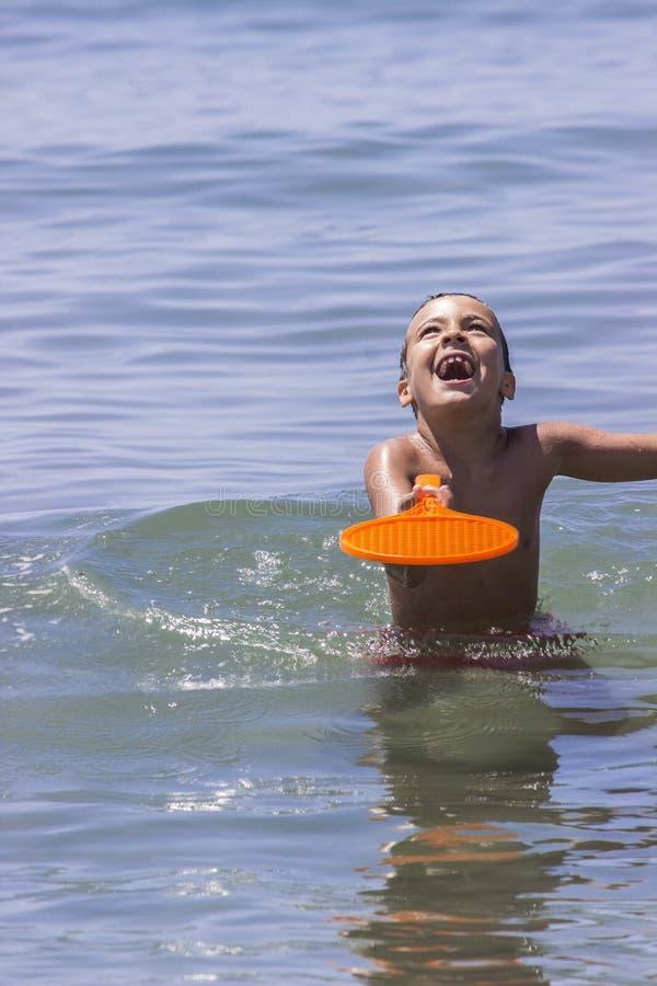 Muchacho que juega en el agua con un raquet imagenes de archivo
