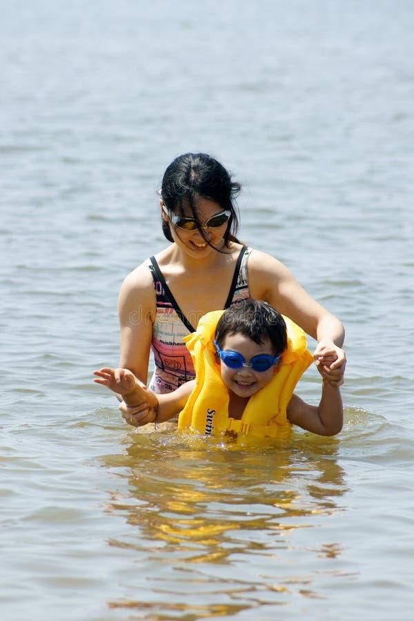 Muchacho que juega en el mar con la madre fotografía de archivo libre de regalías