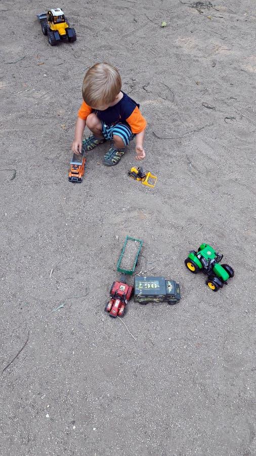 Muchacho que juega en la arena con los coches fotografía de archivo